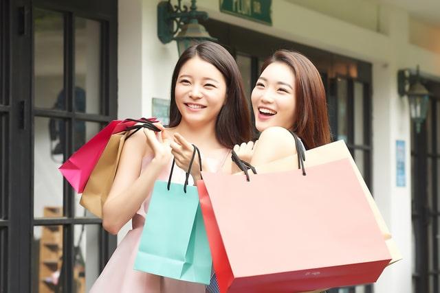 買い物袋を掲げる外国人観光客